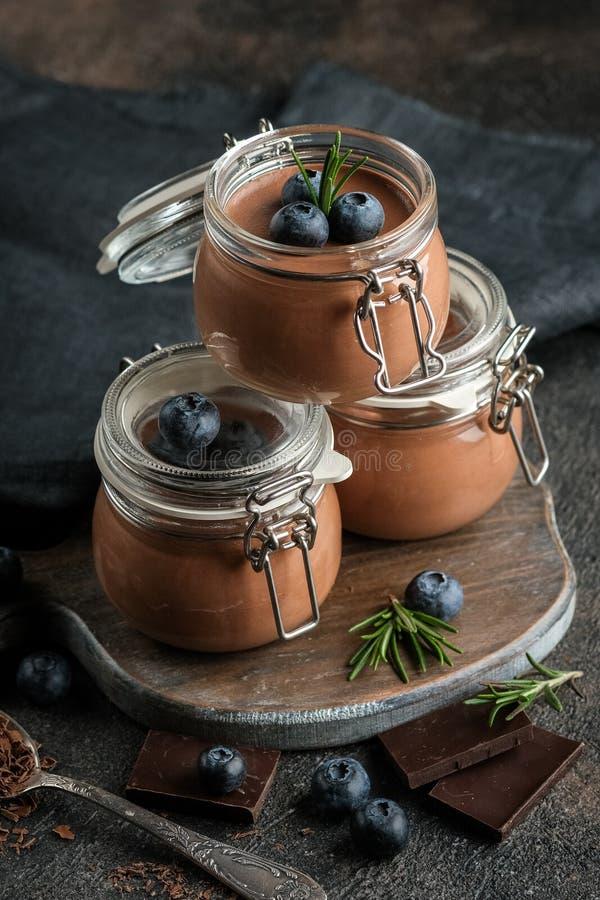Mousse de chocolate en frasco de vidrio con bayas foto de archivo