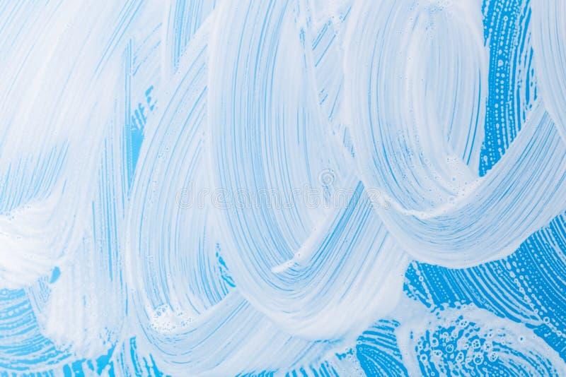 Mousse de détergent sur le fond en verre bleu photo libre de droits