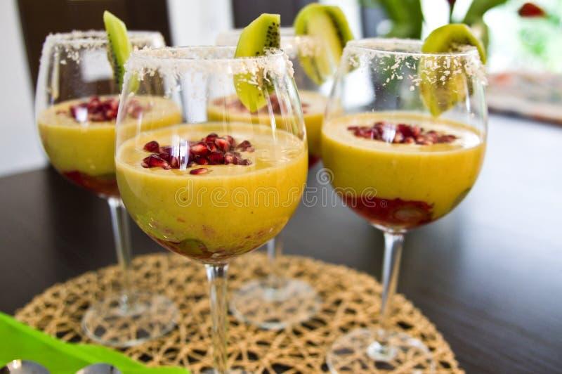 Mousse del mango in vetri di vino con i semi del melograno e del kiwi immagini stock