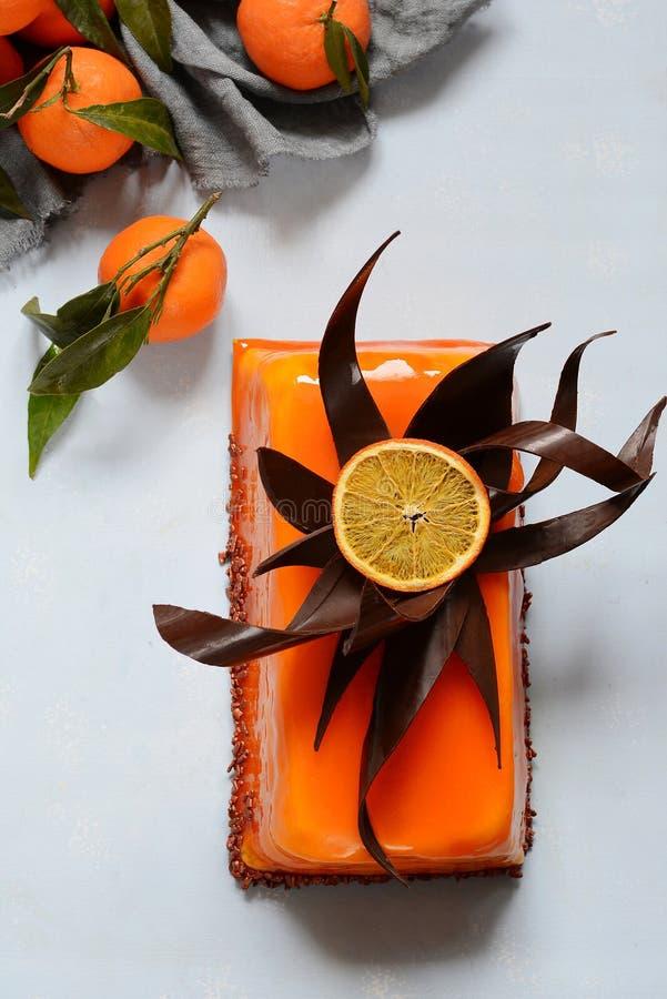 Moussekakan med vaniljkräm och den orange spegeln glasar Chokladdekor Gourmet- delikat efterrätt FruktParfait arkivfoto