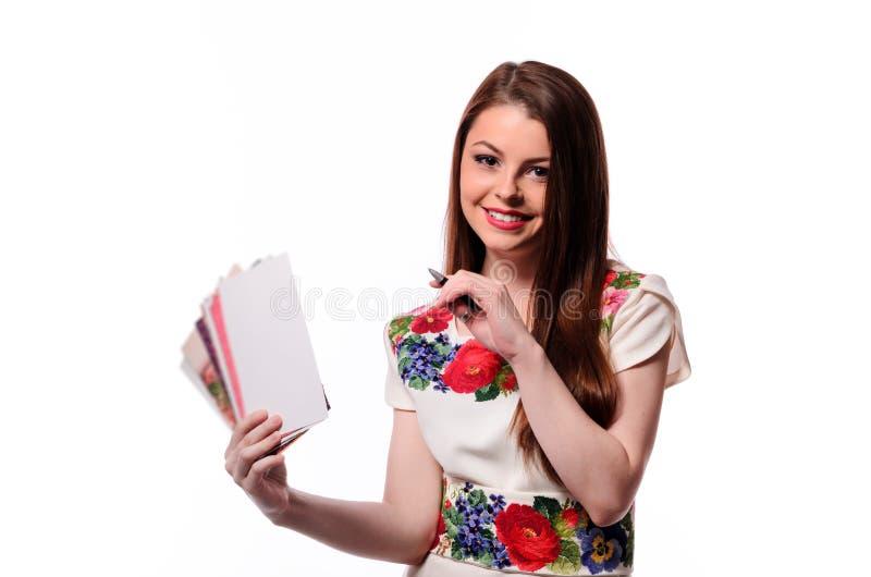 Mousserande affärskvinna som rymmer en anteckningsbok isolerad på en vit bakgrund royaltyfria bilder