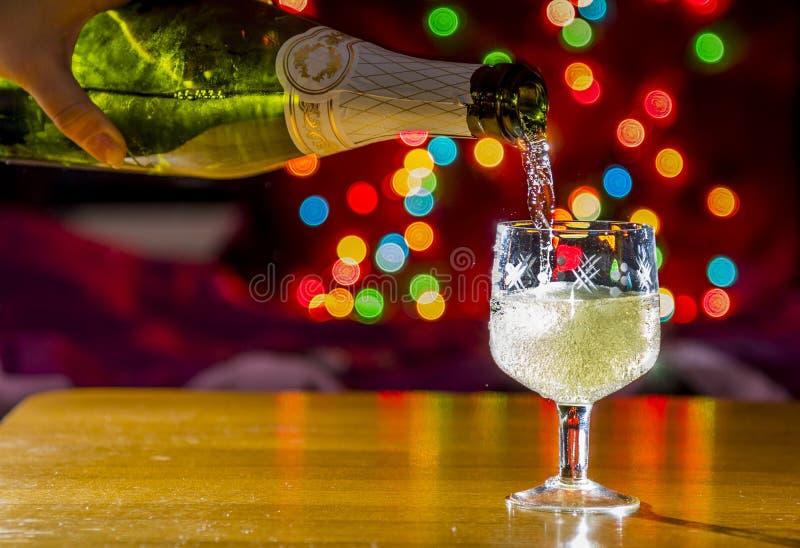 Mousserande vin hälls in i exponeringsglaset royaltyfria foton