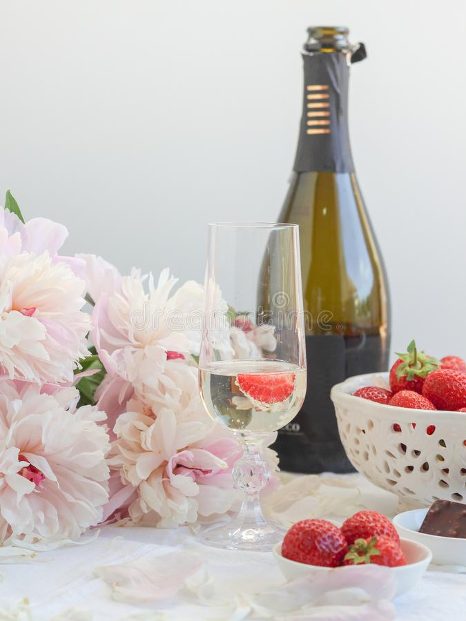 Mousserende wijn met aardbeien voor een verjaardagsontbijt en pioenen op de achtergrond royalty-vrije stock fotografie
