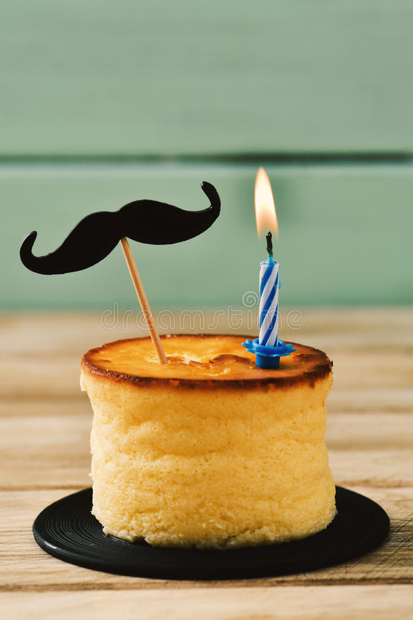 Moustache and lit candle on a cheesecake stock images