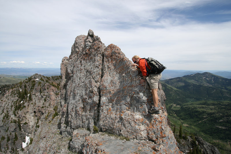 Moutaineer / hike / climb. Hiker nears the top with a few more climbing moves to make along a balancy arete stock photos