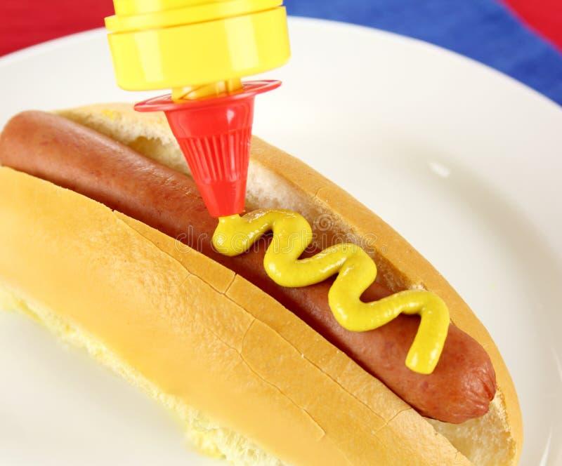 Moutarde sur le hot-dog photo stock