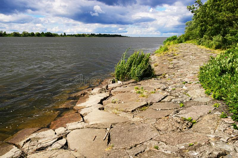 The mouth of the Vistula River to the Baltic Sea with a stone river embankment on a sunny day. stock photography