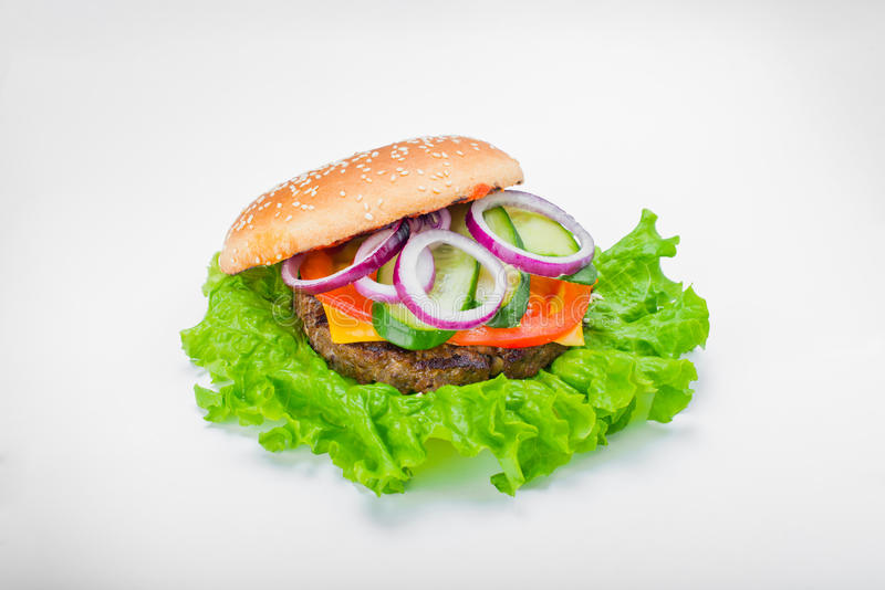 Mouth watering Burger with greens pickles onion. Juicy Burger meat cheese greens pickles onion cucumber on white background stock images