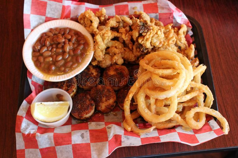Mouth watering image of fried clams, onion rings, sea scallops and baked beans on table at restaurant royalty free stock images