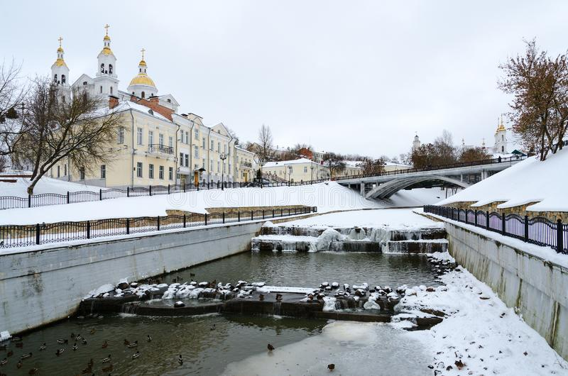 Winter river Vitba and view of Holy Assumption Cathedral and Pushkin Bridge, Vitebsk, Belarus. Mouth of winter river Vitba and view of Holy Assumption Cathedral stock image