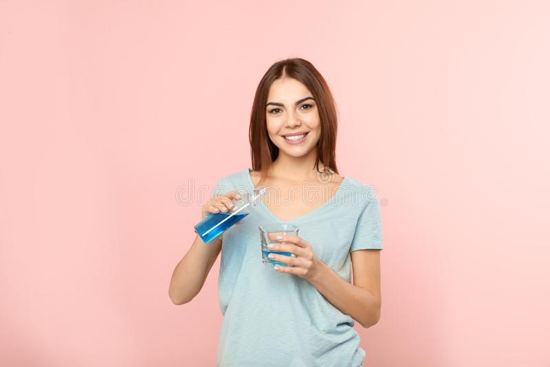 Mouthwash красивой женщины лить от бутылки в стекло на предпосылке цвета стоковые фото