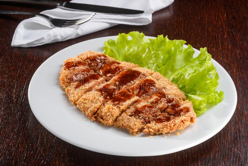 Mouthwatering pork in Japanese breading. In close up of the camera. Yummy piece of meat with Tonkatsu sauce on a leaf of lettuce royalty free stock photography