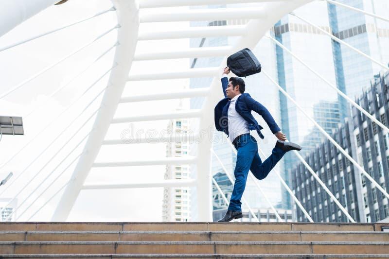 Mouvement brouillé de l'homme d'affaires asiatique, qui tenant la serviette et sautant dans la ville à célébrer ses affaires réus image stock
