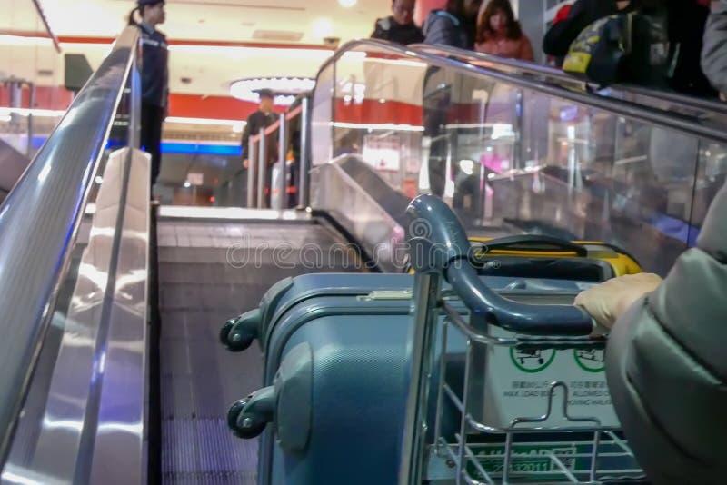Mouvement des personnes poussant le bagage sur l'escalator mobile à l'intérieur de l'aéroport international de Taoyuan photos libres de droits