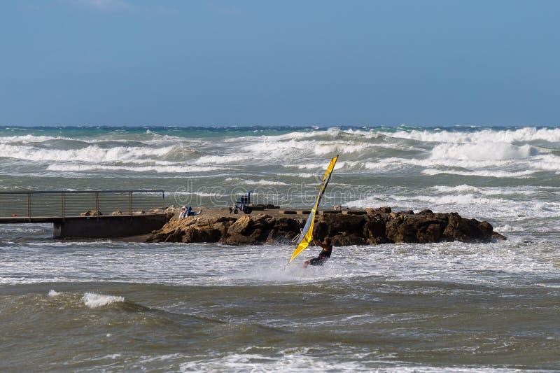 Mouvement et calme, vagues de mer et mer variable en Windy Day : Planche à voile dans l'action et femme agée photos stock