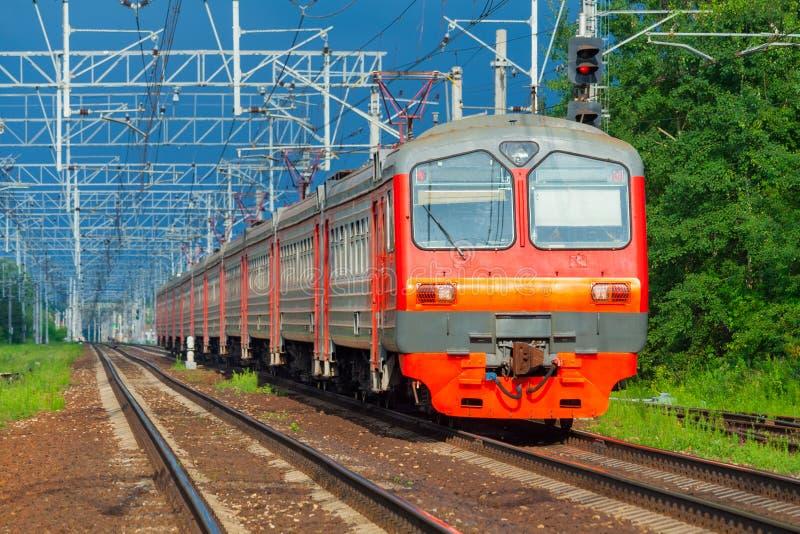 Mouvements de train électrique de passager sur un fond de forêt verte et de ciel bleu-foncé photos libres de droits