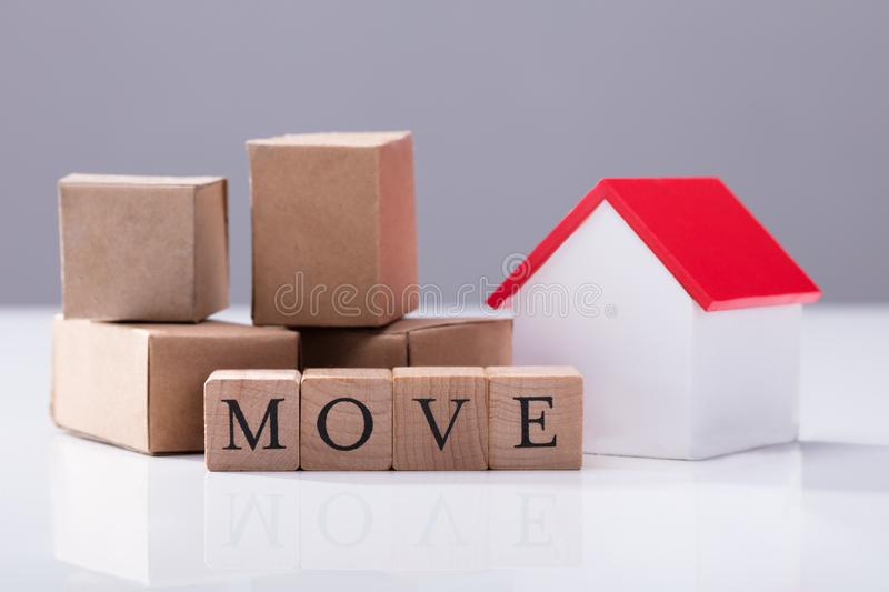 Move Text In Front Of Cardboard Boxes And House Model stock photos