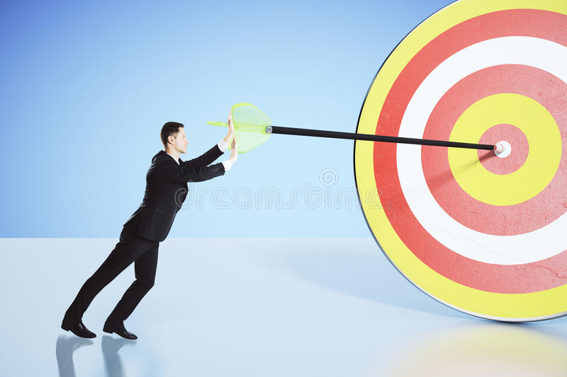 Move towards your goal concept with businessman pushing an arrow. Into the bullseye royalty free stock photo