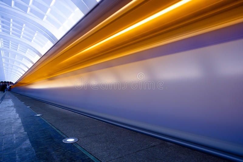 Move trains with orange lights. On underground platform royalty free stock photography