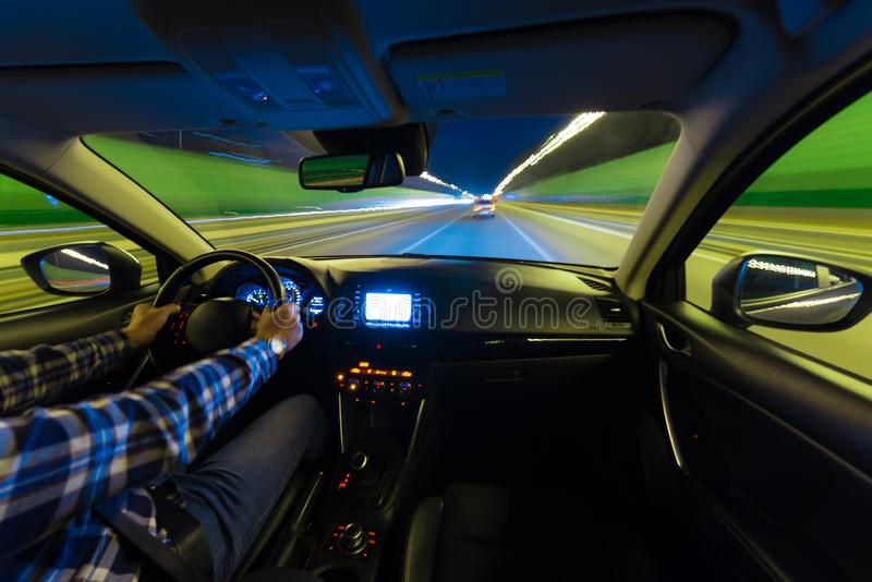 Movement of the car at night at a speed view from the interior, Brilliant road with lights with a car at high speed. The car`s movement at night with a kind of stock photography