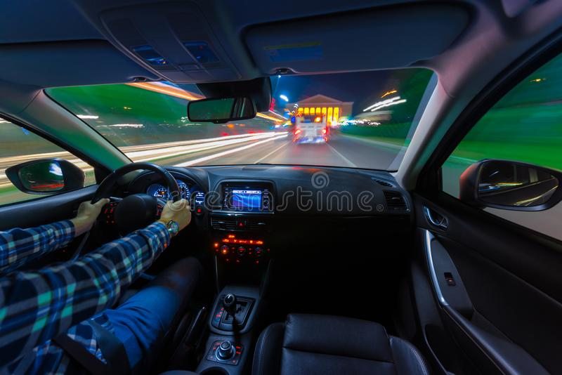 Movement of the car at night at a speed view from the interior, Brilliant road with lights with a car at high speed. The car`s movement at night with a kind of stock images
