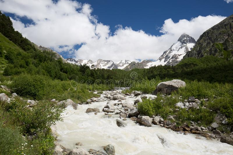 Movement of clouds and water flows in a stormy river in the Caucasus mountains in summer. Russia. Movement of clouds and water flows in a stormy river in the stock photography