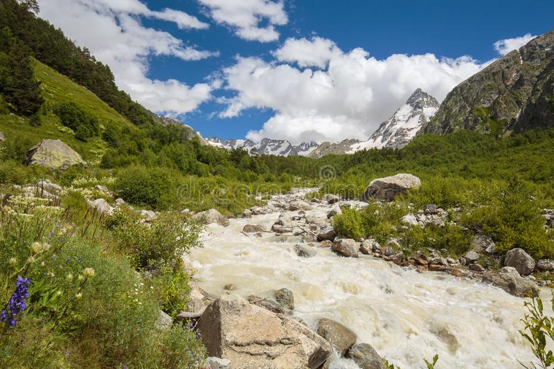 Movement of clouds and water flows in a stormy river in the Caucasus mountains in summer. Russia. Movement of clouds and water flows in a stormy river in the stock image