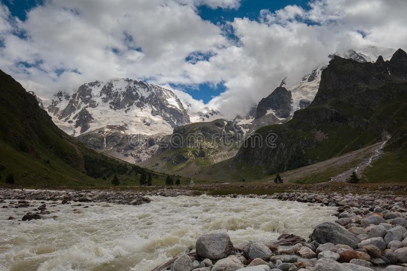 Movement of clouds and water flows in a stormy river in the Caucasus mountains in summer. Russia. Movement of clouds and water flows in a stormy river in the stock photos