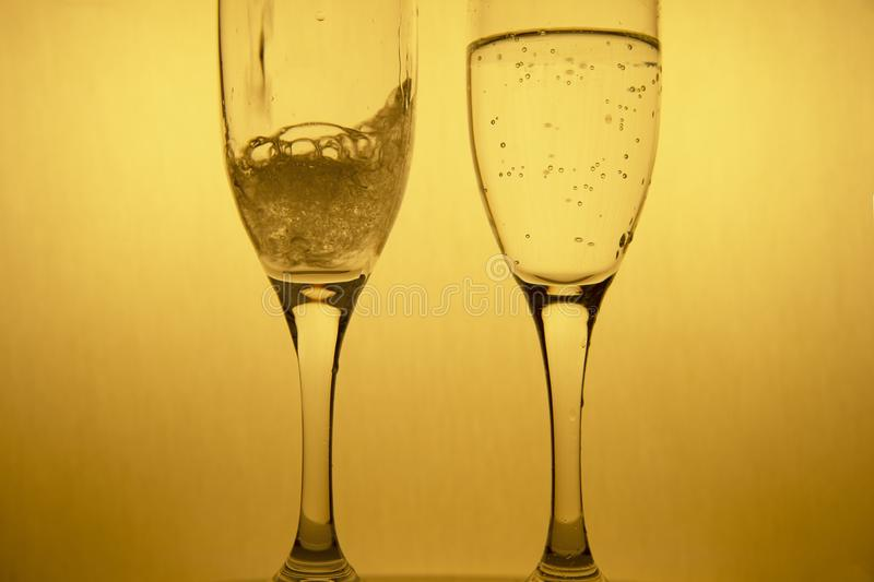 Movement of poring alcohol drinking in couple golden champagne glasses for luxury Christmas celebration party background stock photography