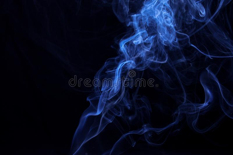 Movement of smoke on black background, blue smoke background, picture on wallpaper, design concept royalty free stock images