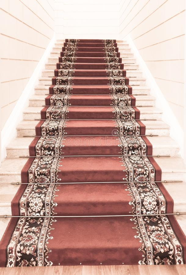 Movement up the front stadget with a red carpet at the end of which light. The front-classical interior with the stairs stock photos