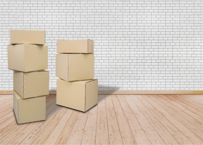 Movendo-se na casa ou no apartamento novo, sala vazia offic com as caixas da caixa de Brown fotos de stock