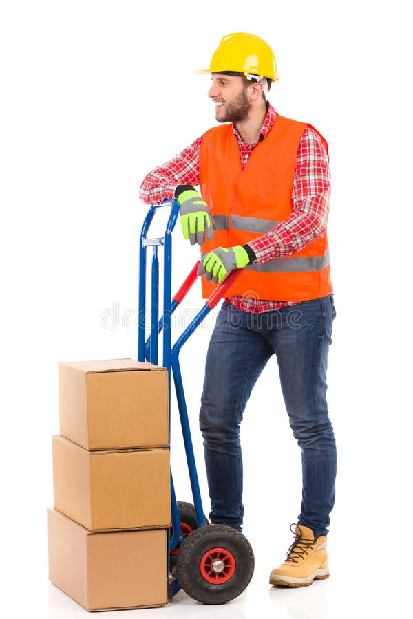 Mover and delivery cart. Smiling man in yellow hardhat and orange reflective vest posing with a delivery cart and looking away. Full length studio shot isolated stock photography