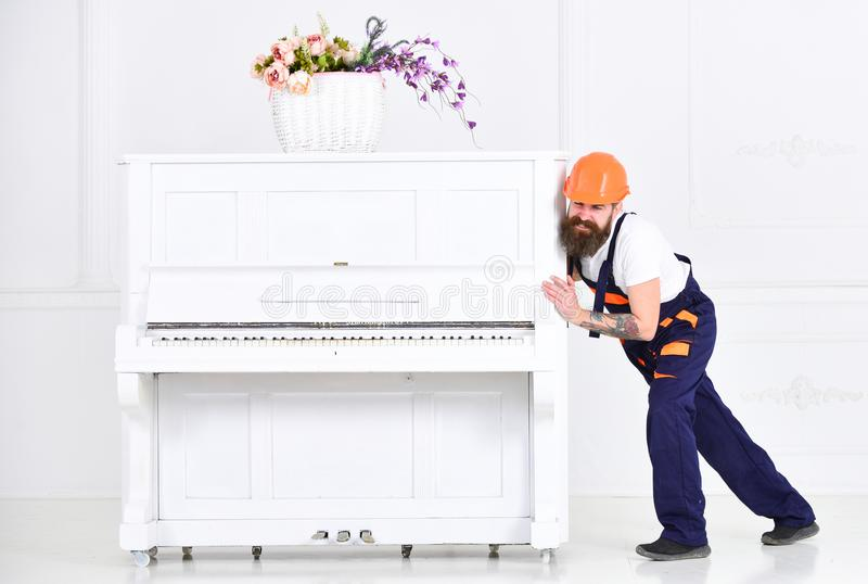 Mover frowning while moving heavy piano. Tired guy relocating stuff in the apartment on white background. Home stock photography