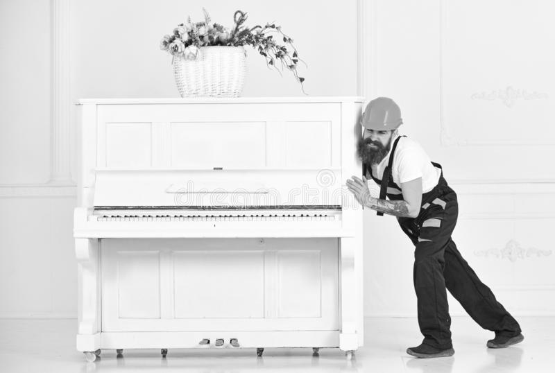 Mover frowning while moving heavy piano. Tired guy relocating stuff in the apartment on white background. Home royalty free stock images