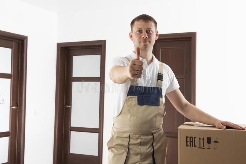Mover holds thumb up. Relocation services man. Loader in house with cardboard boxes royalty free stock photography