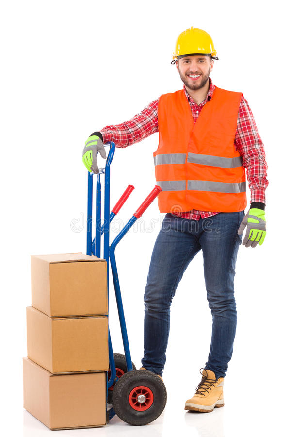 Mover posing. Smiling man in yellow hardhat and orange reflective vest posing with a delivery cart and looking at camera. Full length studio shot isolated on royalty free stock photos