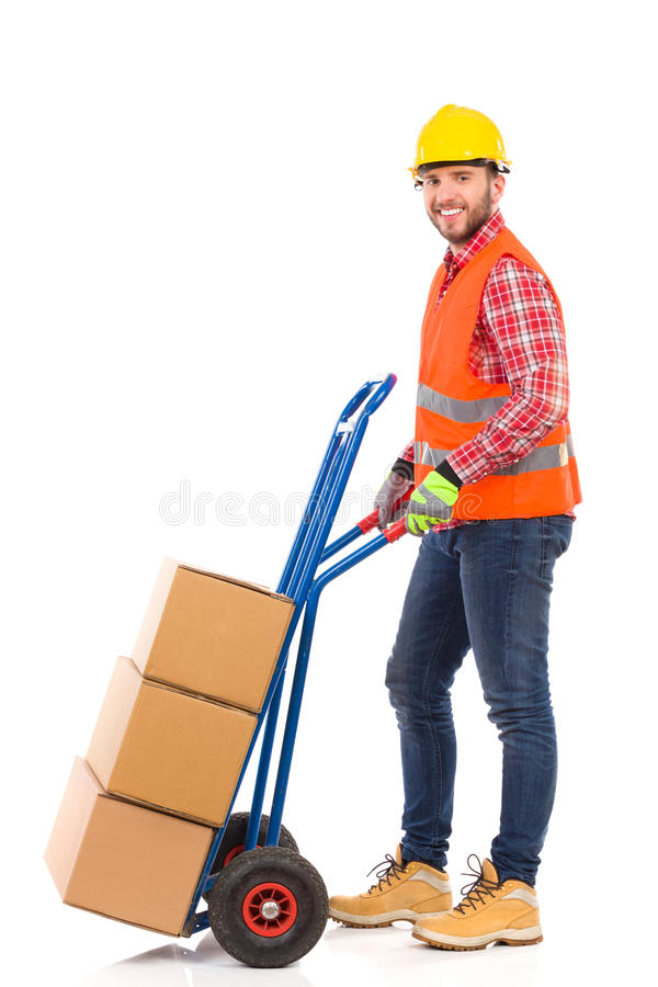 Mover with a push cart. Smiling man in yellow hardhat and orange reflective vest pushing a delivery cart. Full length studio shot isolated on white stock photography