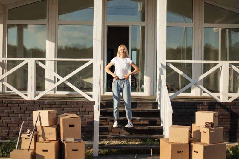 Mover-se para a HOME nova mulher que começa vida nova As caixas de cartão aproximam a escada fotos de stock royalty free