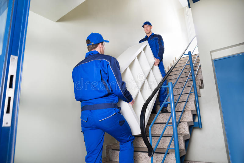 Movers Carrying Shelf While Climbing Steps At Home royalty free stock image