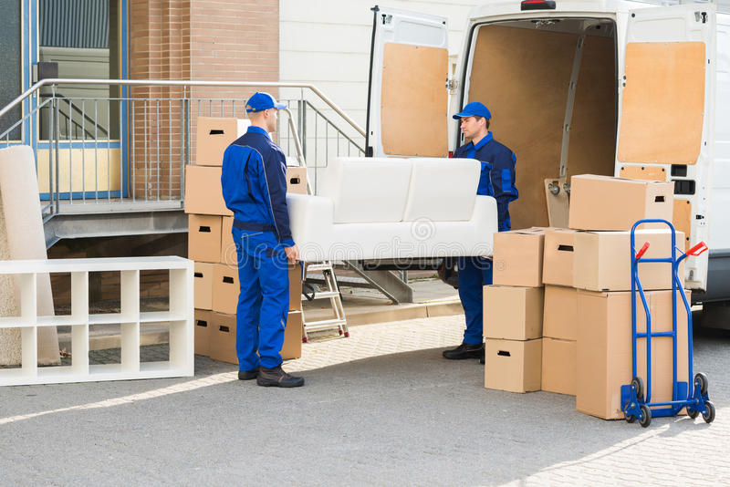 Movers Carrying Sofa Outside Truck On Street stock photos