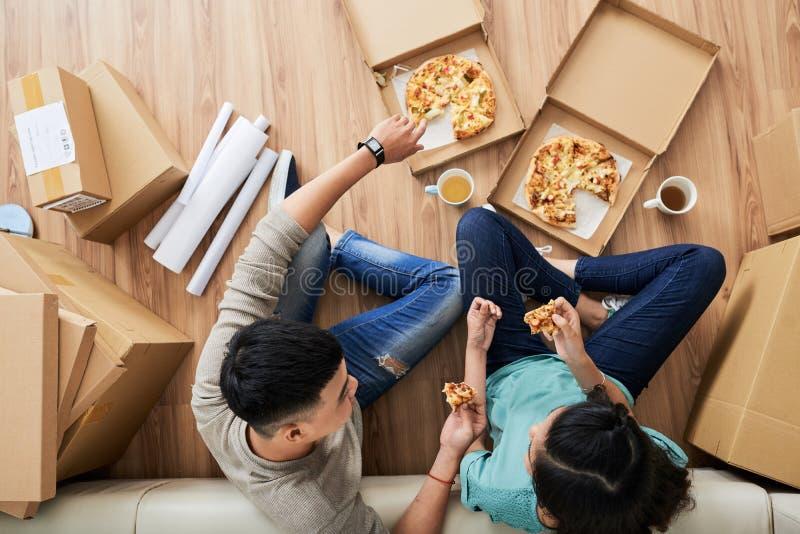 Movido nos pares da casa nova que comem a pizza fotos de stock royalty free