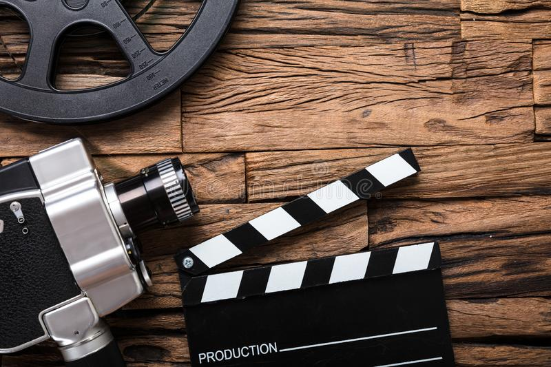 Movie Camera With Film Reel And Clapper Board On Wood royalty free stock photos