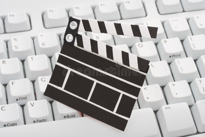 Movie clap board and keyboard. A black colour movie clap board on top of a white computer keyboard. Metaphor for online movie viewing and downloads stock images