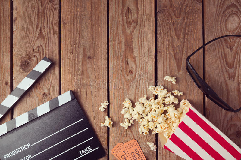 Movie clapper board, 3d glasses and popcorn on wooden background. Cinema concept stock images