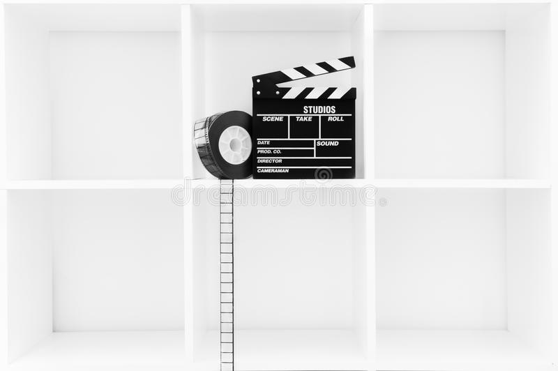 Movie clapper board and film reel on white bookshelf. Movie clapper board and 35 mm film reel on white cubical bookshelf with empty copy space royalty free illustration