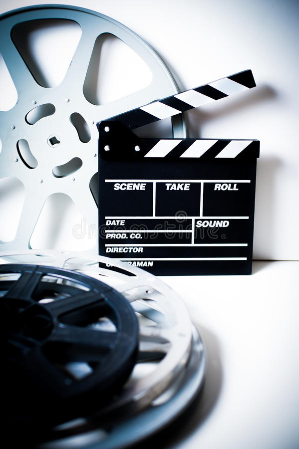 Movie clapper with film reels on white. Movie clapper with vintage empty film reels on white background vertical frame royalty free stock photo