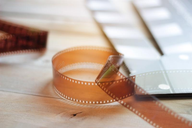 Movie clapper and film strip on wooden background royalty free stock photo