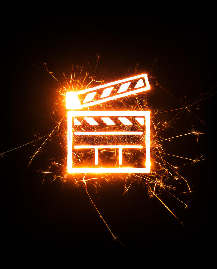 Movie clapper in glowing sparks on dark background. stock image