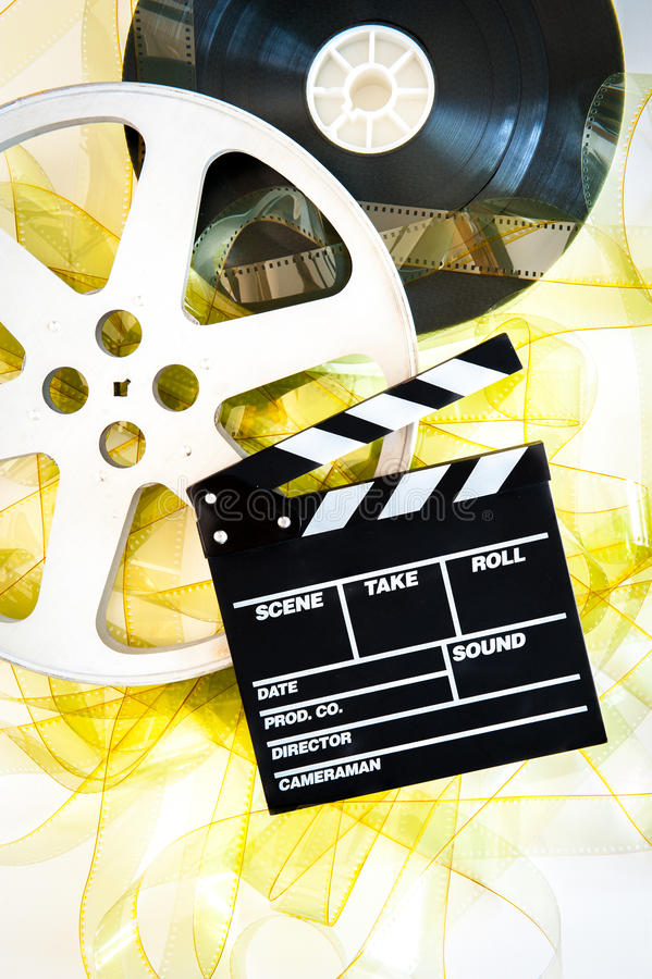 Movie clapper on 35 mm cinema reels unrolled yellow filmstrip. On white background vertical stock photography